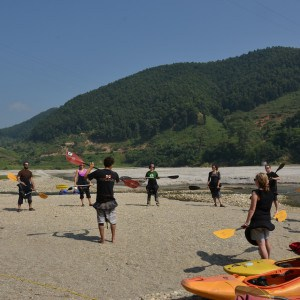 People standing in circle holding kayak paddles on sandy beach with kayaks on the ground