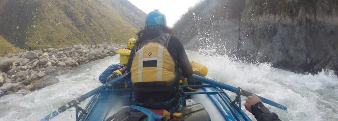 guide holding oars white water splashing around the boat rafting a rapid on a river